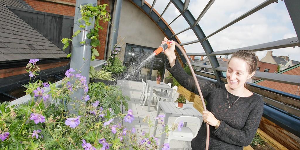 Aisling Ní Labhraí watering the community garden on the rooftop of the Cultúrlann