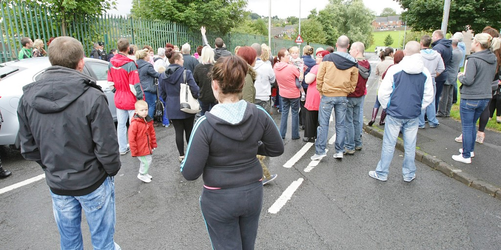 Worried parents arrive on the scene to collect their children during yesterday's bomb alert, only to find they were being kept in the school for their own safety