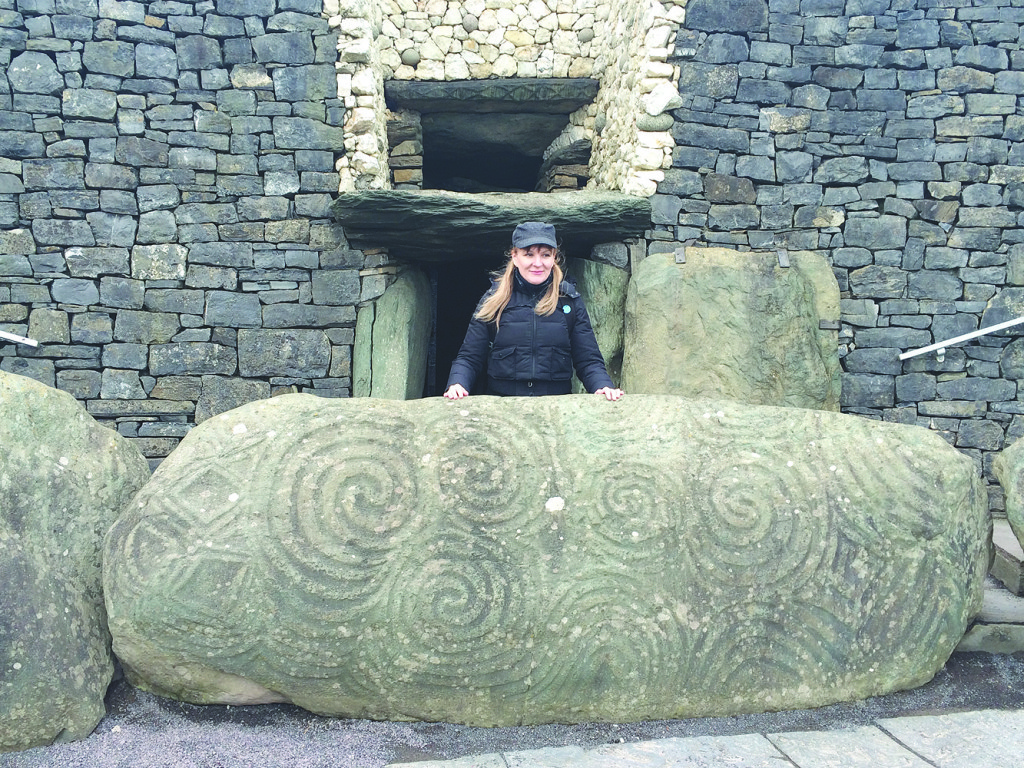 The writer standing behind one of the inscripted stones at the base of the Newgrange mound