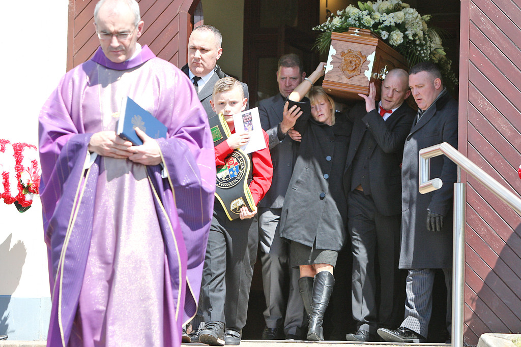 Eamonn Magee Snr and his wife Mary carry the coffin of their son, Eamonn Jnr, from St Joseph's Hannahstown, for burial in the adjacent cemetery. Leading the way is Parish Priest Father Kevin McGuckien