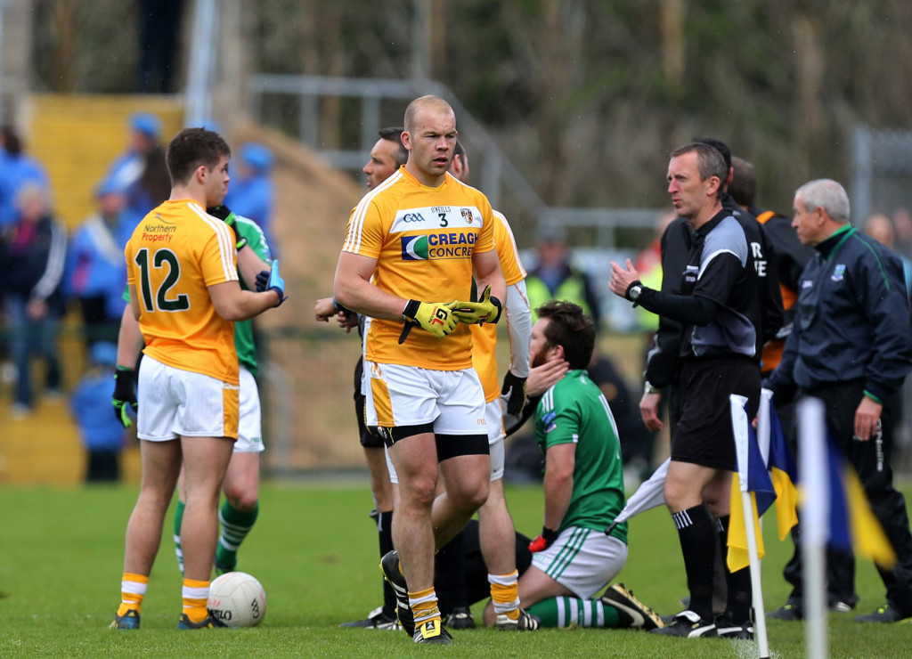 Ciarán Flaherty receives attention as Sean McVeigh makes the long walk after his 31st minute red card