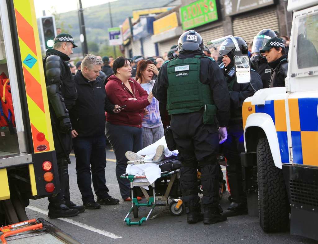 Distressed relatives look on as a 16-year-old girl is taken to an ambulance after being trapped under a car at Ardoyne yesterday. With them is Father Gary Donegan