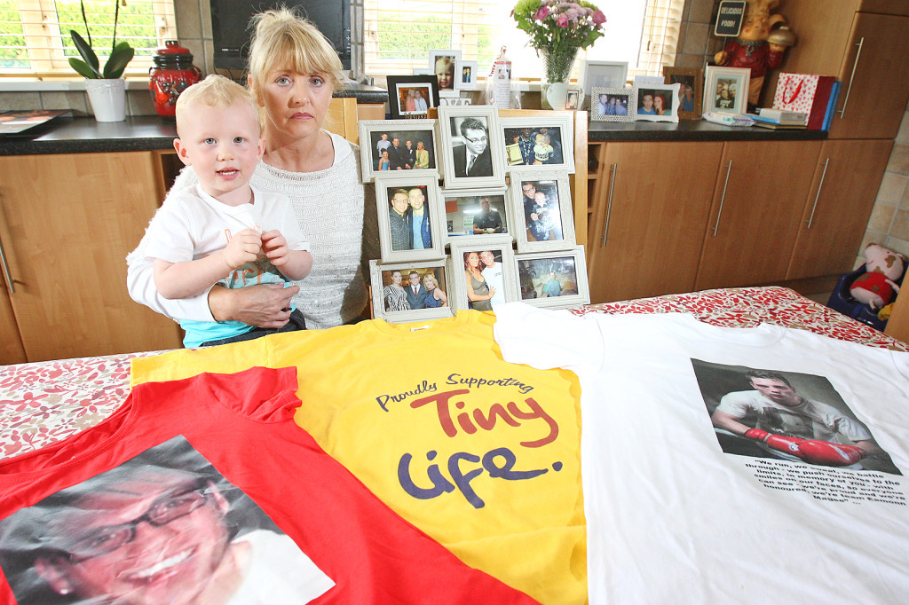 Mary Magee and her grandson Cormac with photographs of Eamonn