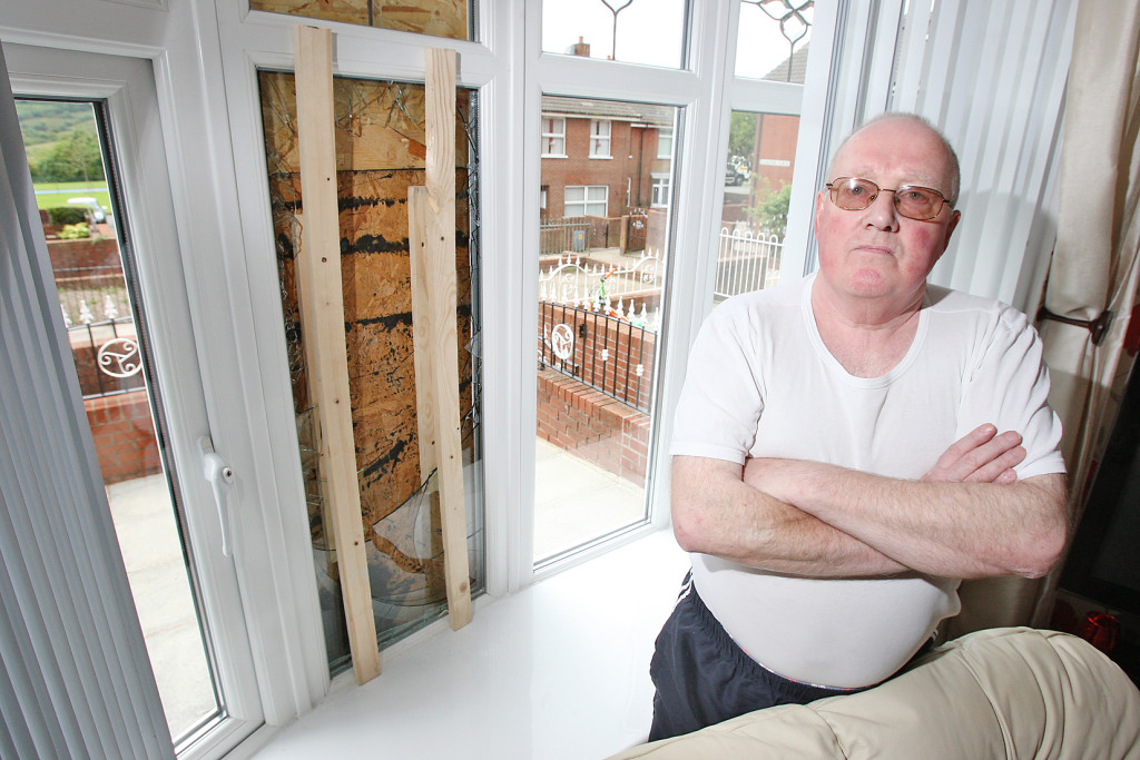 Joe Deans beside the shattered window at his house in Flaxton Place, Ligoniel