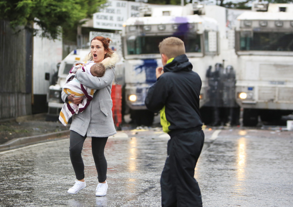 Shauna Bradley brings her friend's baby to safety after fire broke out at a house near the scene of the rioting
