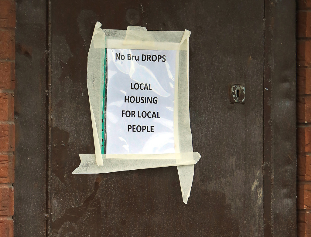 One of the posters taped to the window of a Housing Executive property in Tigers Bay
