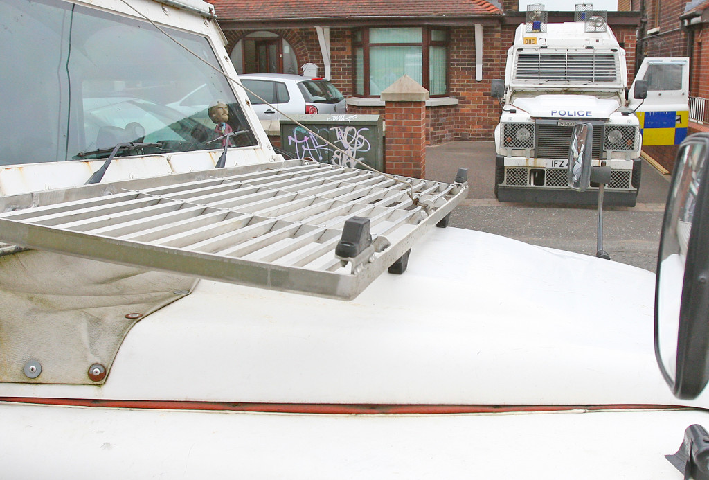 MODEL OPERATION: The PSNI raid Bobby Storey's Andersonstown home yesterday after his arrest. Bizarrely, plastic models of Ron Burgundy, the central character in the hit comedy 'Anchorman' – a parody of the media – were on display on the dashboards of these two Land Rovers