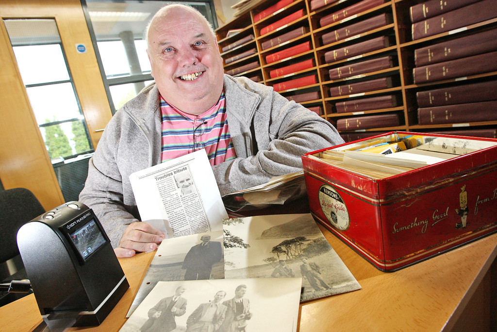 James McCabe examines some of Joe Nolan's extensive archive; he's holding a picture of the poet and archivist