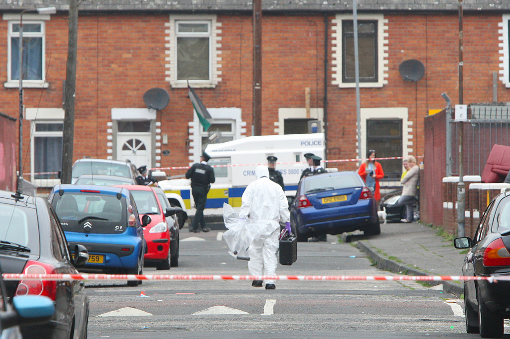 A police forensics officer removes the pipe-bomb device from the scene of yesterday's alert in Rodney Drive
