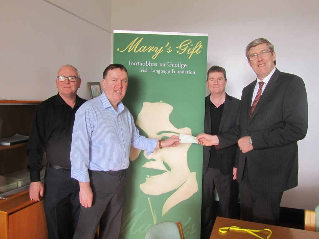 Minister for Education John O'Dowd hands over the cheque from Mary's Gift to Pilib Ó Ruanaí, who is joined by Jake Mac Siacais, Forbairt Feirste, and Seán Mistéil, chair of Forbairt Feirste