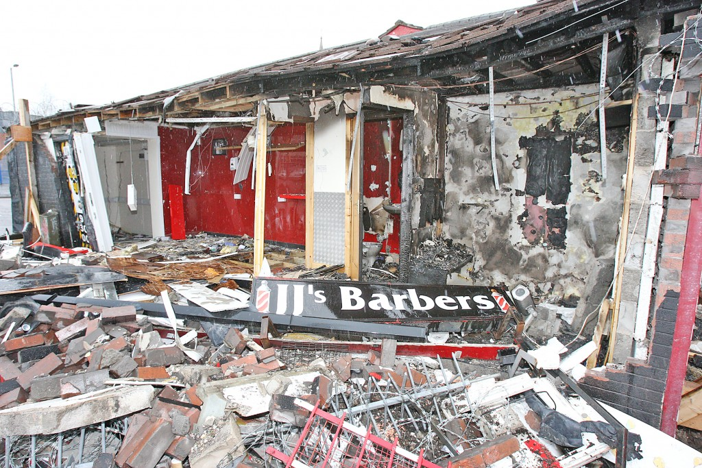 The scene of the arson attack which gutted a barbers and taxi depot on the Glen Road