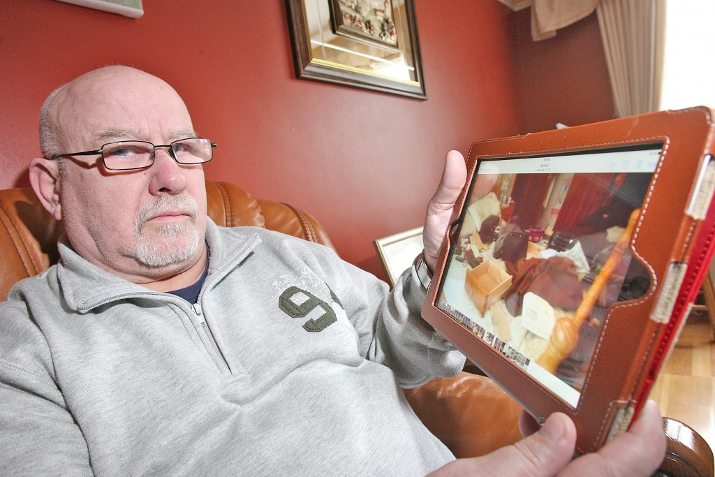 Devastated: Tony Gibson with an image of the ransacked bedroom on his iPad