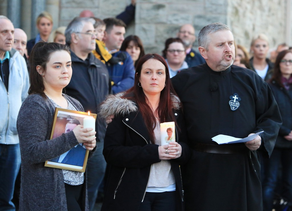 Michael McGibbon's wife Joanne McGibbon and daughter Seana with Fr Gary Donegan at the vigil in the grounds of Holy Cross Church, Ardoyne