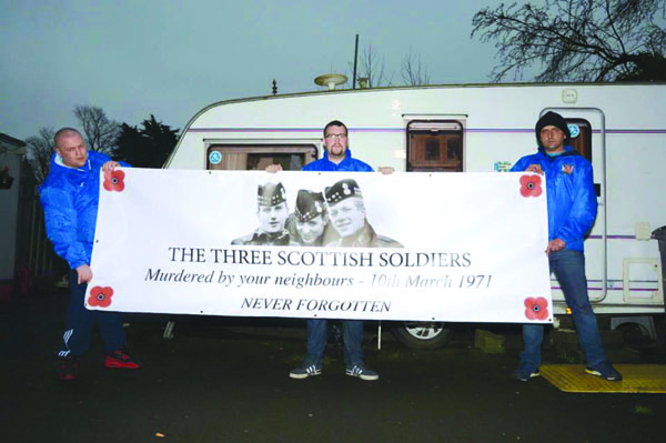 Members of the Regimental Blues hold up a banner to three British soldiers killed in Ligoniel in 1971 at Camp Twaddell