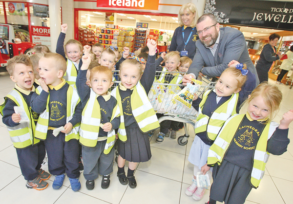 Cathedral Nursery pupils receive goodie bags from Kennedy Centre manager John Jones on their visit to the shopping centre. Also pictured is Principal Una Barr
