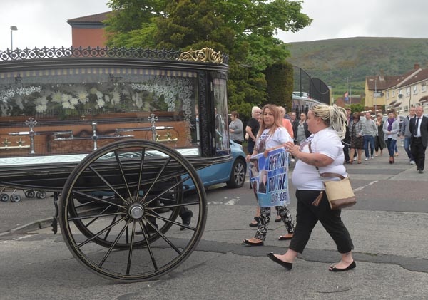 Family members lead the funeral cortege as it makes its way through Turf Lodge yesterday