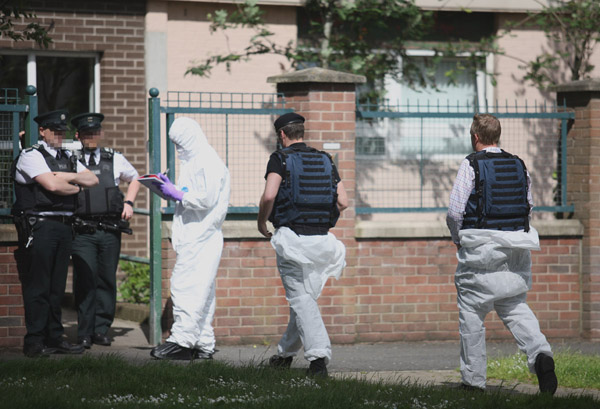 Police and British army bomb disposal experts at the scene of the find in the New Lodge