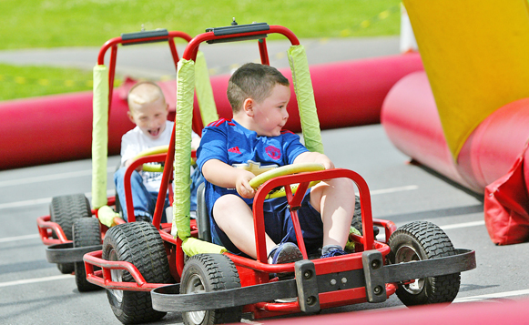 Ruari Fitzsimons takes AJ Harper on the back straight during a Falls Youth Providers Family Fun Day in Dunville Park as part of the Falls Summer Scheme