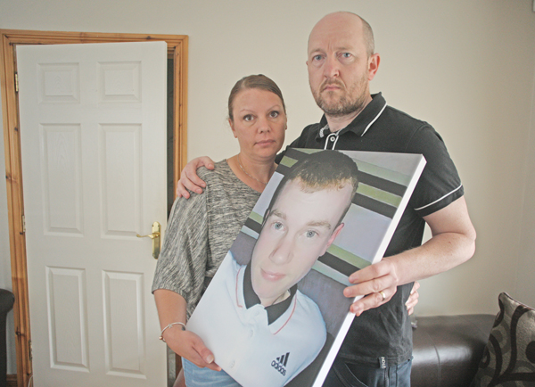 Sarah and Paul Fox with a photo of their son Aaron at their home in Thornberry