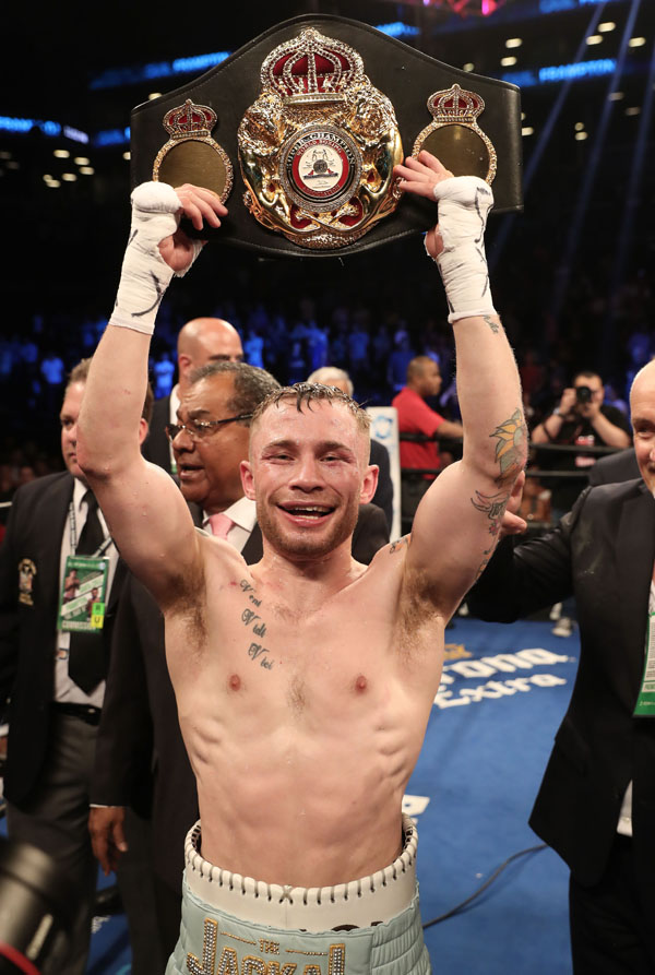 Carl Frampton holds the WBA featherweight title belt aloft after Saturday night's victory over Leo Santa Cruz in New York