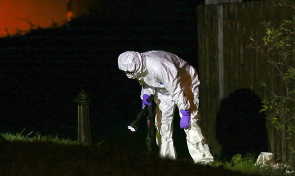 A forensic officer looks for clues following the Poleglass shooting  Pic by Kevin Scott