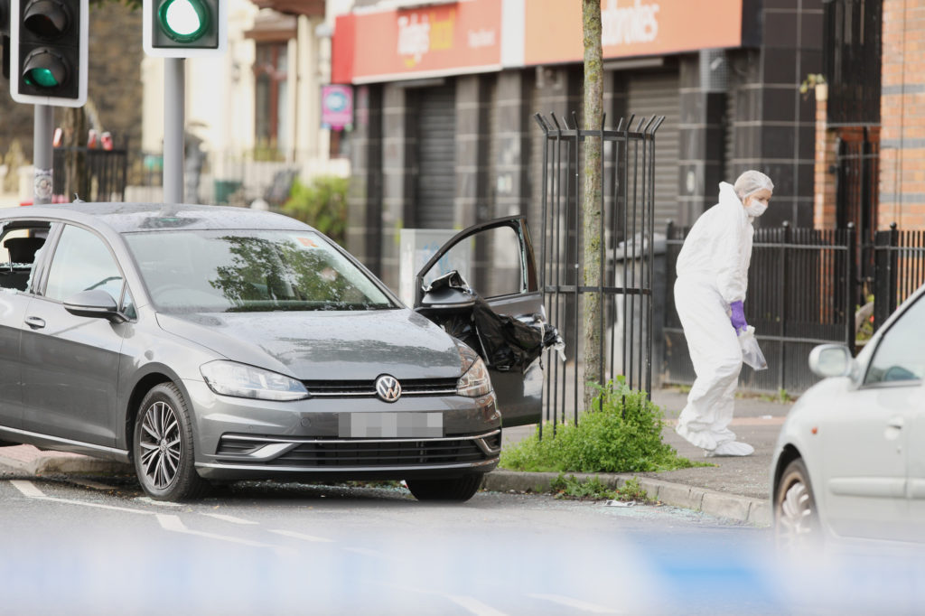 EXPLOSION: A PSNI forensics officer beside the car that was damaged in the pipe bomb attack
