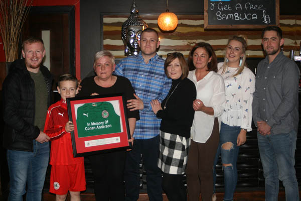 Former Reds star George McMullan and Nathan Farmer from Cliftonville U12s present the family of Conan Anderson with a signed framed jersey