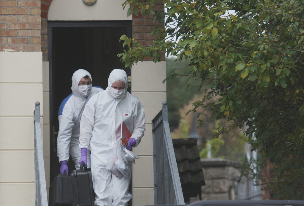 Police forensics officers leave the flat where the woman's body was found