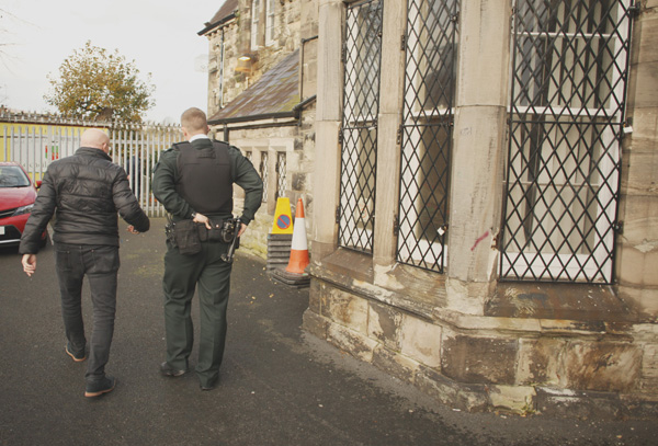 A PSNI officer joins Rev Bill Shaw to survey the damage