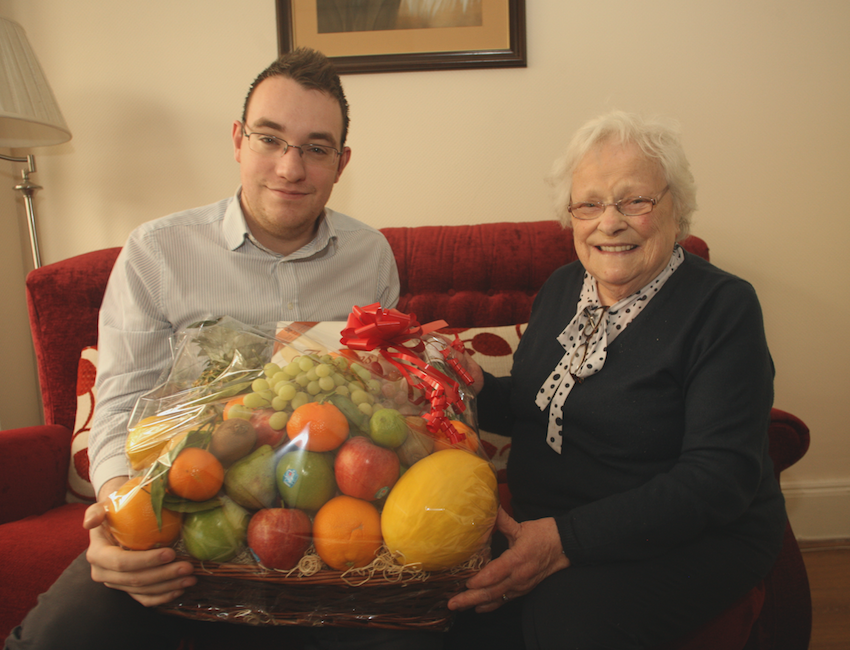 KIND-HEARTED:Conor McParland from the North Belfast News hands over a Christmas hamper to Olive McAlea that was donated by a local businessman