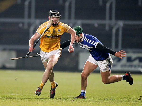Antrim midfielder Joe Maskey slips away from his opposite number, James Ryan during last Saturday's  game in Portlaoise. The Saffrons suffered a five-point defeat to Laois and face a huge task this Sunday when they take on Division 1B pacesetters, Limerick in Cushendall