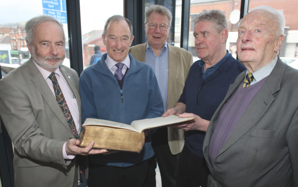 : James E Moffett hands over the Bible from Broadway Presbyterian Church – which is now  An Chultúrlann McAdam Ó Fiaich – to Kevin Shannon, with Very Rev Michael Barry, Derek Alexandar, and Rev Jim Stothers looking on