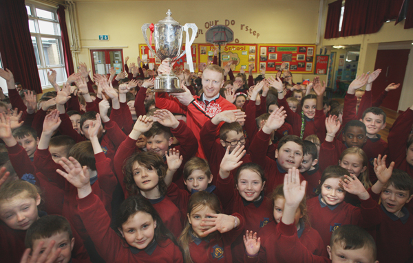 L‡amh Dhearg senior footballer Brendan McComb with the Senior Championship cup at St Oliver Plunkett Primary School