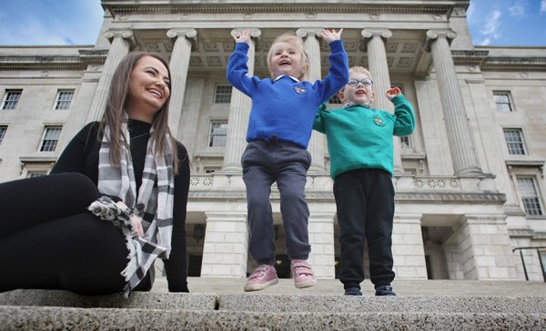 Nursery teacher Erin O'Reilly with Amelia Skillen and Ethan Huddleston from Stanhope Street nursery school on the steps of Parliament Buildings Stormont. The North Belfast nursery received a Derrytrasna Award for outstanding pastoral care from the Department of Education and Public Health Agency