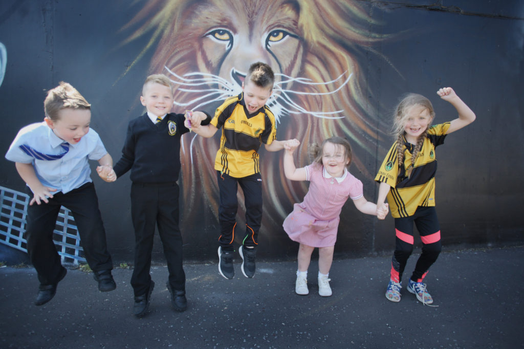 Patrick Hughes, Conláed Hughes, Niamh McConnell, Mason McAdorey and Emily O'Kane jump for joy at a new mural in Bawnmore Drive in Belfast