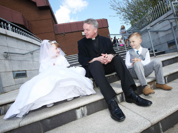 Kyra and Jaden Lynas celebrating their First Communion with Fr Thomas McGlynn at St Agnes' Church