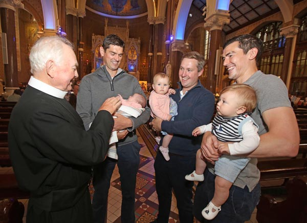 At the Clonard Novena blessing of Babies and Children are Fr John Hanna with Paddy Turley and his one month old daughter Erin, Michael McKeown with his daughter Katey and Matt McManus with his son Finn