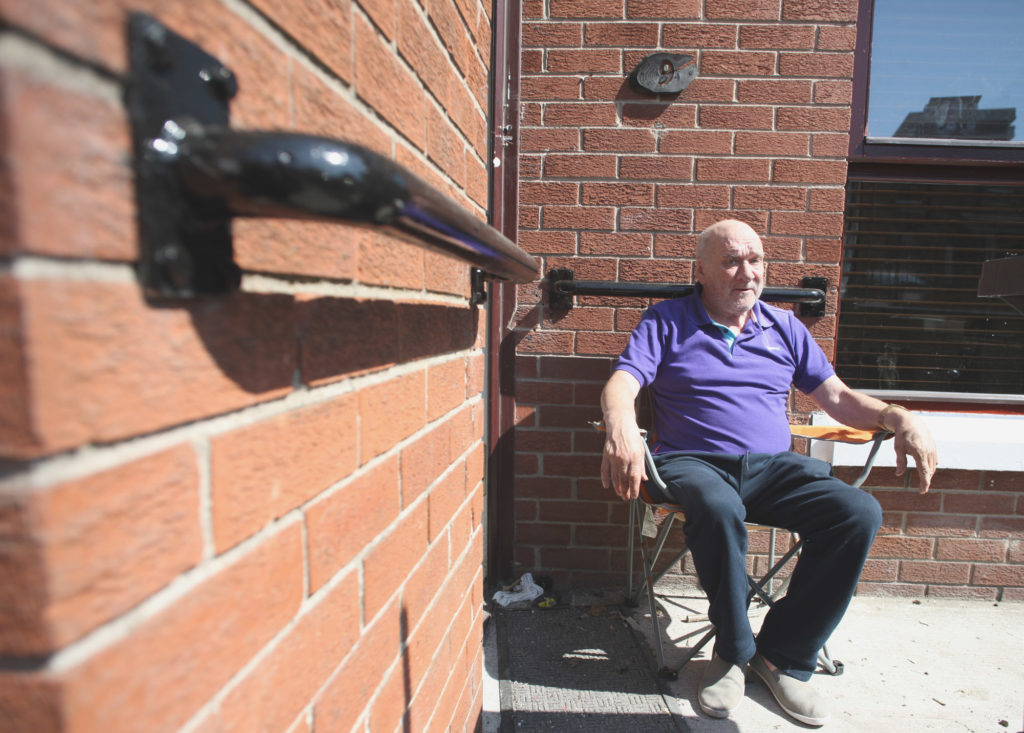 ASSAULT: Sean Benson sitting outside his New Lodge home this week