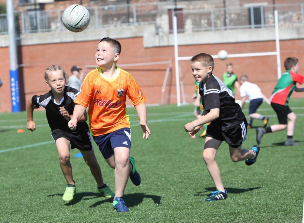 Aidan Mailey, Aaron Maguire and Antoin Mallon in a tussle for the ball at the Ardoyne Kickhams Cúl Camp at the Cricky