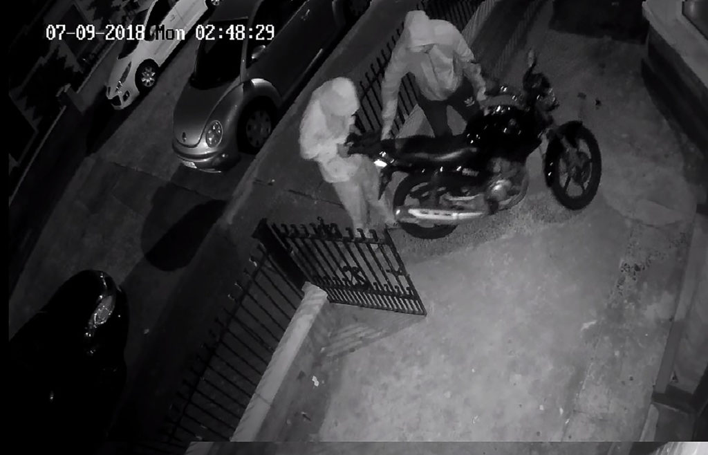 The thieves caught on CCTV taking bolt cutters to the motorcycle's padlock