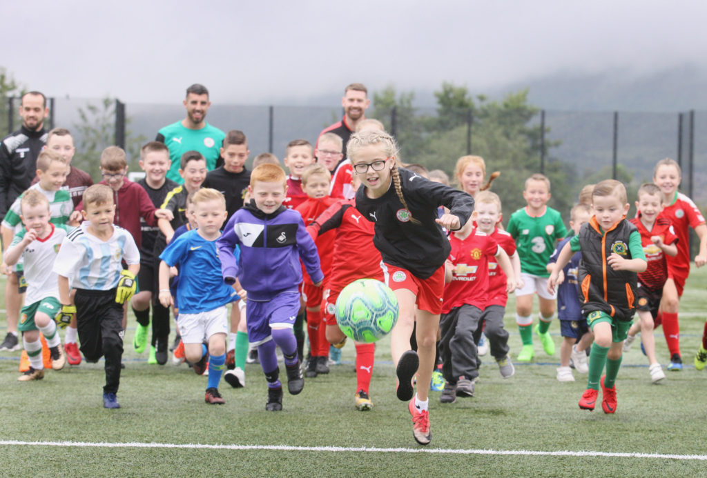 Lucy Loughens kicks off the Mini-World Cup at the Bone Hills pitches as part of the Ardoyne and Bone Festival. Looking on are a number of top Irish League players who gave up their time to come along and pass on some valuable coaching tips