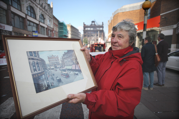 Roberta Johnston on High Street holds a painting of Bank Buildings, while behind her the Primark fire at the famous building is being doused by firefighters this morning