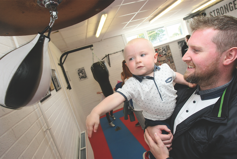 Stephen Agnew and baby John Agnew (grandson of John Dunne) testing out the equipment at the Whiterock Leisure Centre boxing suite in memory of the late John Dunne.
