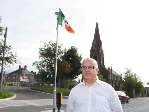 Tim Attwood at the Glen Road spot where the flags have been erected