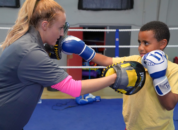 Seconds out:  Coach Lauren Leonard puts junior boxer Daniel Mervyn through his paces at Corpus Christi Boxing Club on the Whiterock Road, using equipment funded by the Housing Executive. The club will host the Antrim Amateur Boxing Championships from September 25 to 27