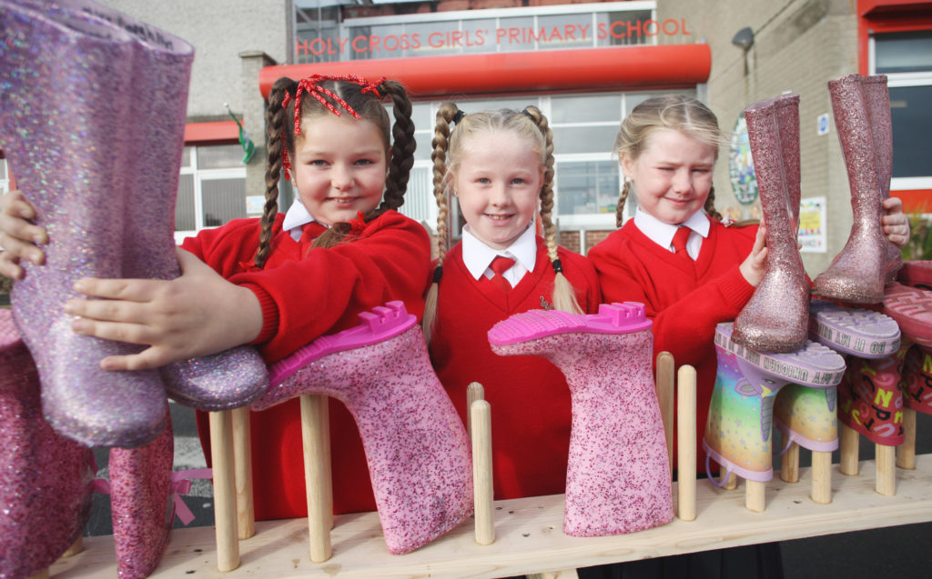 Holy Cross Primary School girls Chloe, Ellie Rose and Cliona trying out the new welly boot holder made by Men's Shed and delivered to the school