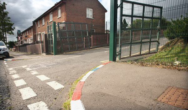 Red white and blue painted kerbs outside Holy Cross Girls PS on Ardoyne Road