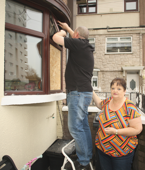 Phyllis Gregg and Sean O'Neill repair the damage to their New Lodge home after another attack