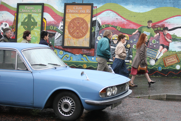 Extras walk past a classic 1968 Triumph 2000 MK2 during filming for the BBC's Dublin Murders in Lenadoon this week