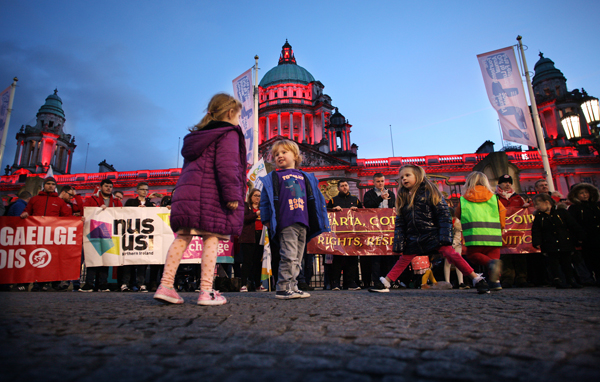 Children laugh and play while the City Hall is lit up red in support of Irish language rights